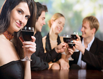 Dressed up mid-aged people drinking a dark liquid in wine glasses
