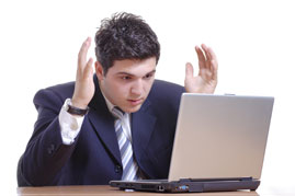 Man getting visibily frustrated with a laptop